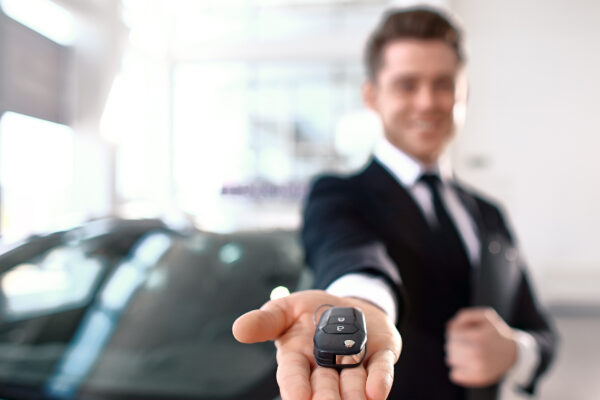 Formal wearing young salesman offers brand new car key. Close up of the key In the foreground. Focus on the key.