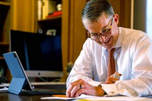 President Jay Hartzell, sitting at desk, orange tie, smile, glasses, tablet, working