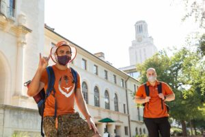 students, hook 'em horns sign, burnt orange shirts, backpacks, masks, tower