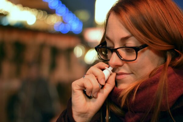 Woman using nose spray
