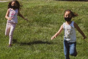 Kids play outside with masks on.