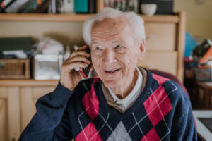 Elderly man talking on phone sitting at home