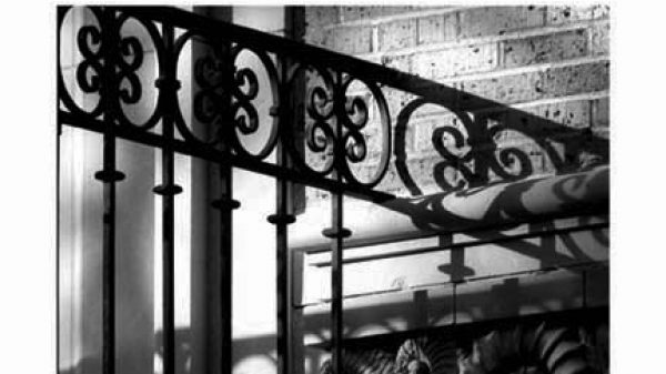 A black and white closeup photo of wrought iron gates and a brick wall with some nautilus shell details.