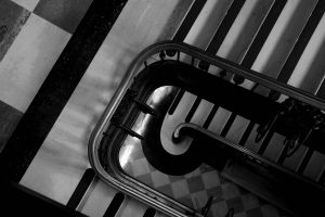 A black and white photo looking down the levels of a grand staircase. There is a checkered floor.