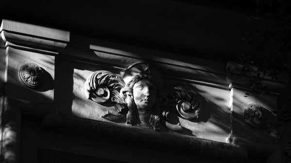 A black and white photo of a wall in shadow. The light is hitting a sculpture detail of a Classical Greek face