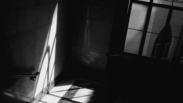 A black and white photo of a staircase landing in shadow. The light from a wind fours a triangular shape on the wall.