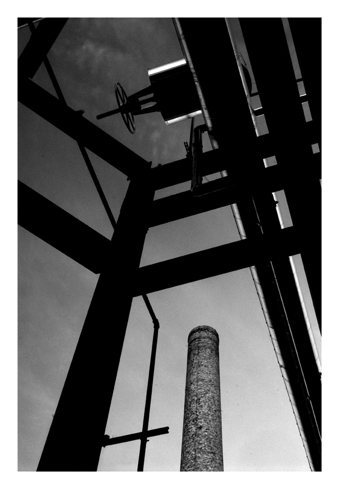A black and white photo  looking up at the chimney stack of a power plant framed by several beams.