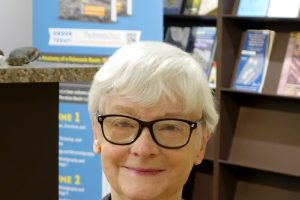 A woman wearing glasses sits in front of some shelves with pamphlets. She has short white hair and wears a striped jacket.