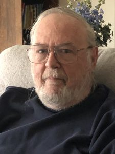A man with a short white beard and glasses sits in a chair.