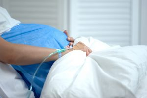 Pregnant woman holding blanket, feeling abdominal pain, risk of miscarriage