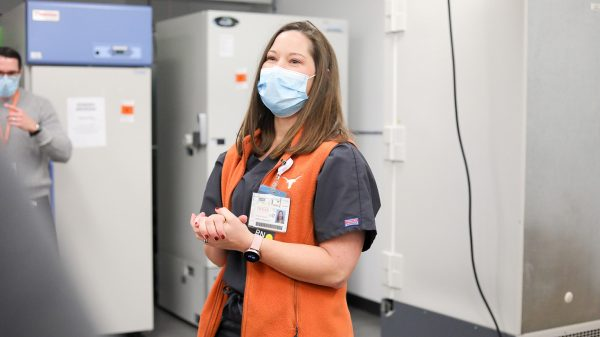 A woman wearing a hospital mask and an orange vest stands before laboratory freezers.