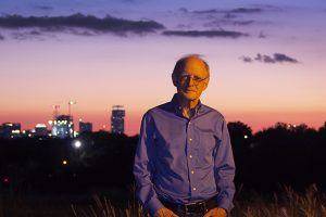 A man stands in a field at dusk with the city skyline behind him.
