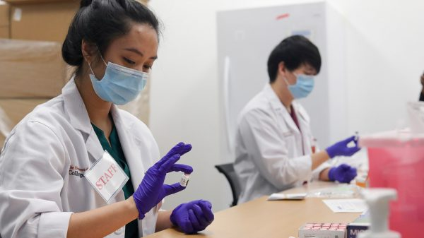 A man and a woman sit at a table preparing vaccines. They each wear medical masks, white lab coats and purple gloves.