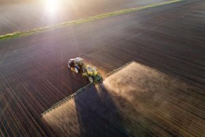 Tractor spraying young crops in field