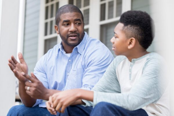 Black father (left) seated and speaking with Black son.