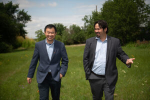 ommunity and Regional Planning Associate Professor Junfeng Jiao (left) and AustinTransportation's Assistant DirectorJason JonMichael (right) walk through a field in the Georgian Acres neighborhood in North Austin where UT and the City of Austin will build a smart mobility hub.