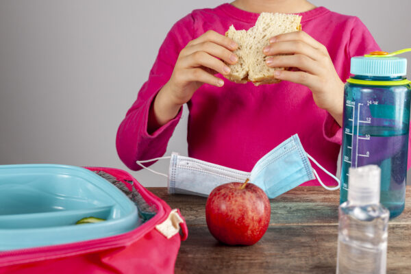 Returning back to school concept after COVID pandemic. A lunch time setting with mask and sanitizers