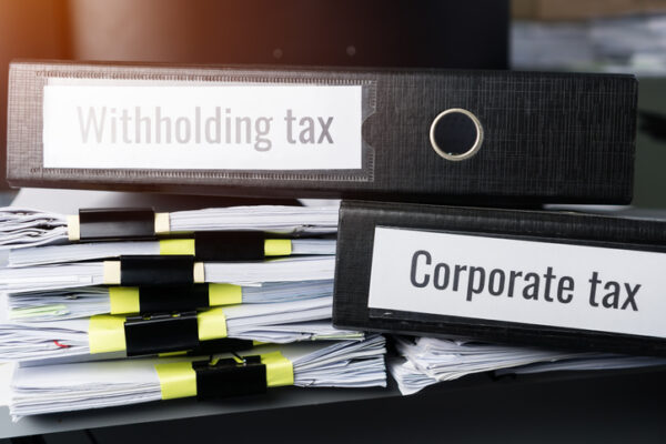 Tax concept, Withholding taxes binders files on document report in business office. Retention taxes is income tax to be paid to government by payer of income rather than by recipient of the income.