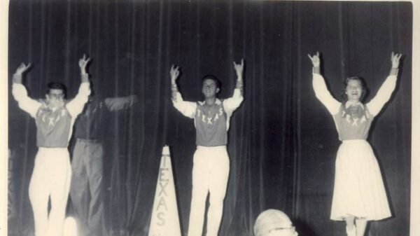Two male cheerleaders and one female cheerleader do Hook'em Horns sign in black and white photo